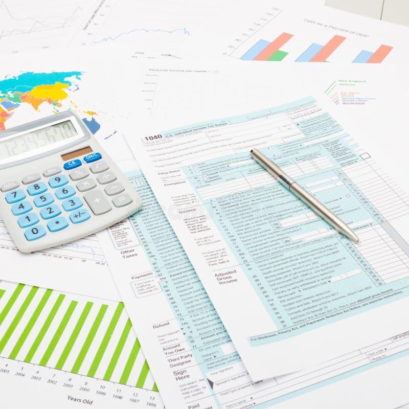 Räknemaskin och penna över skattformen för USA 1040 och några finansiella diagram - nära övre studioskott fotografering för bildbyråer