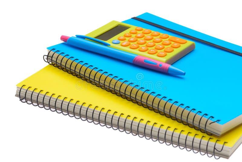 Räknemaskin och penna för bok för gul och blå anmärkning royaltyfria bilder