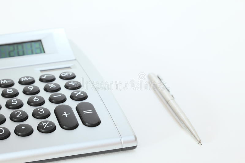 Räknemaskin och penna på skrivbordet royaltyfri fotografi
