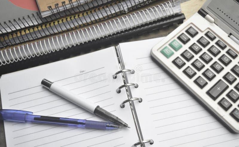Räknemaskin på anteckningsboken med pennan arkivbild