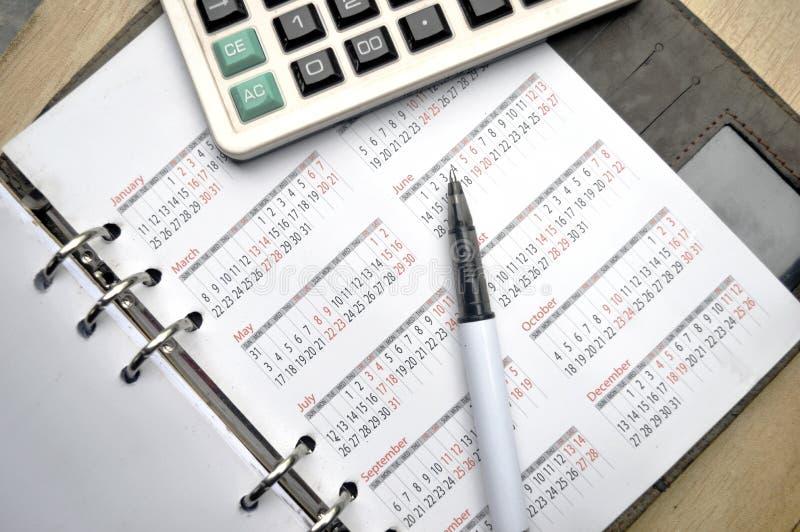 Räknemaskin på anteckningsboken med pennan royaltyfri bild