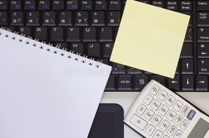 Räknemaskin, smartphone och minnestavla på bärbar datortangentbordet, närbild arkivbild