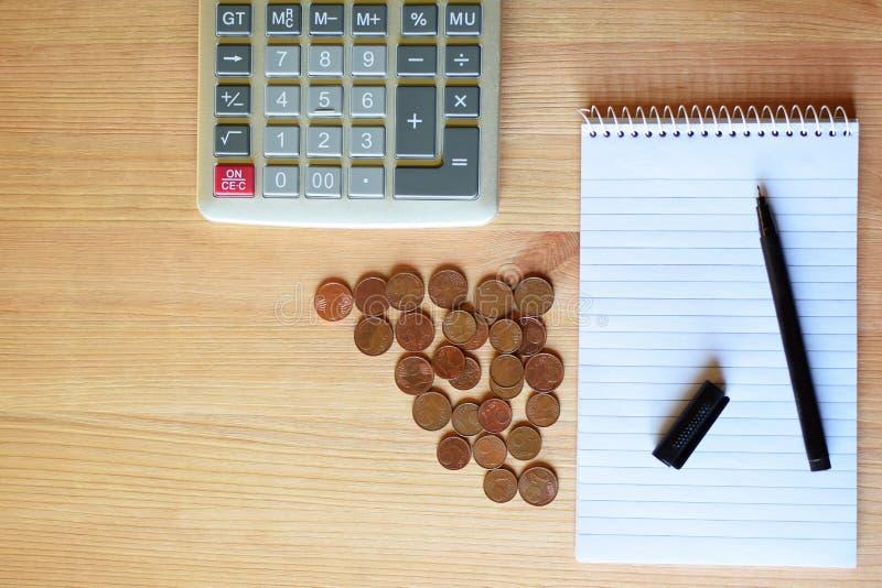 Räknemaskin, tom anteckningsbok, penna och mynt arkivbilder