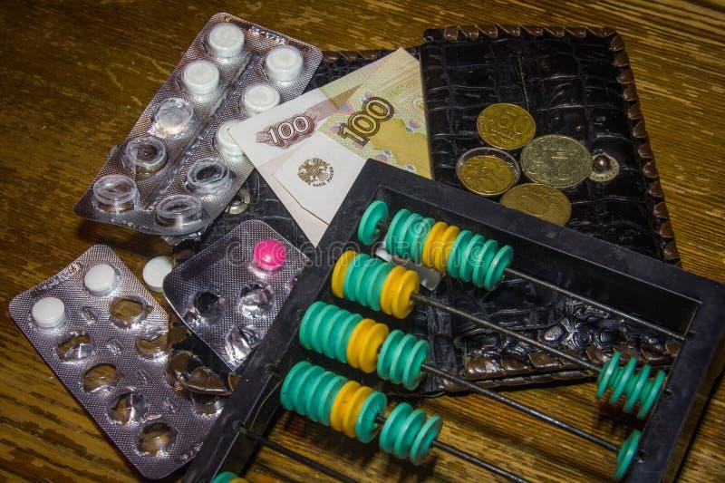Räkningspengar på mediciner på den gamla kulrammet royaltyfri fotografi