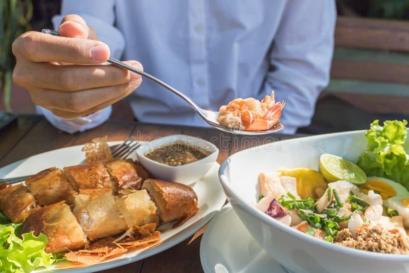 Räkor för skopa för kvinnabrukssked från kryddig havs- sallad i restaurang royaltyfria foton