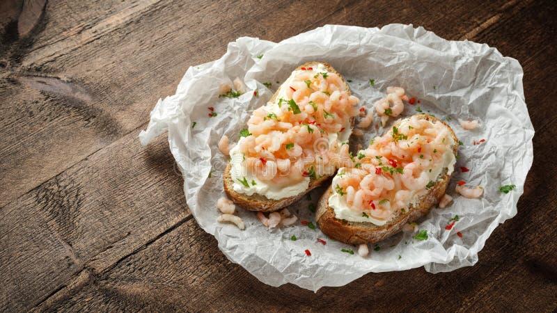 Räkor, havs- bruschetta för räka med krämig ost, persilja och chili arkivbild