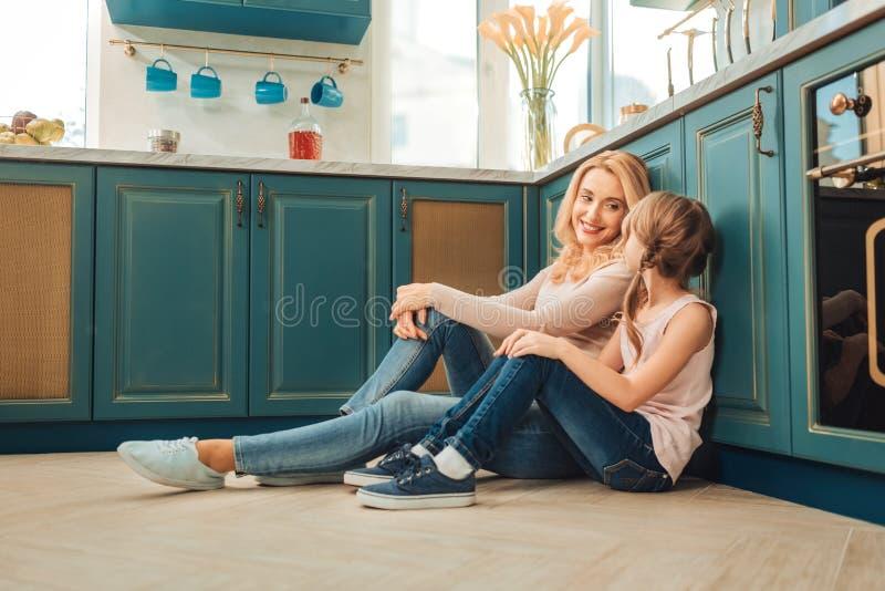 Rätselhafte Blondine, die ihre Tochter betrachten stockfotos