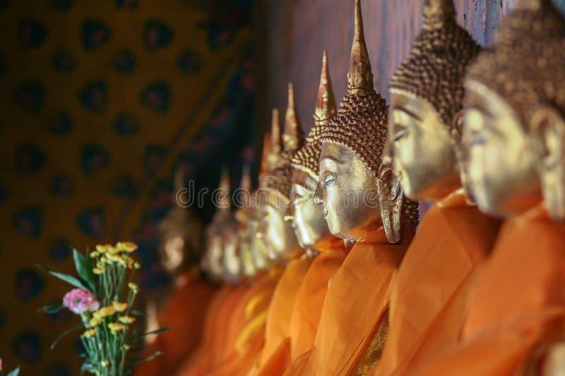 Rätsidasikt av en rad av guld- Buddhastatyer som placeras längs väggen som slås in i orange torkduk arkivfoto
