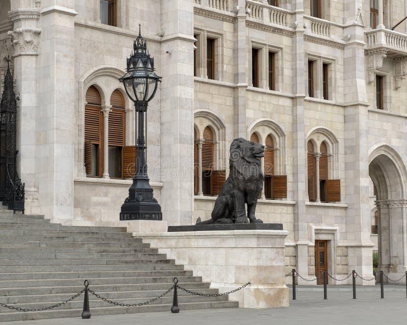 Rätten av två brons lejonstatyer som flankerar den östliga ingången av den ungerska parlamentbyggnaden, Budapest royaltyfri foto