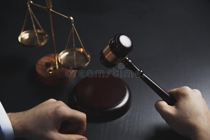 Rättvisa och lagbegrepp Den manliga advokaten i kontoret med mässingsskalan på trätabellen, reflekterade arkivbilder