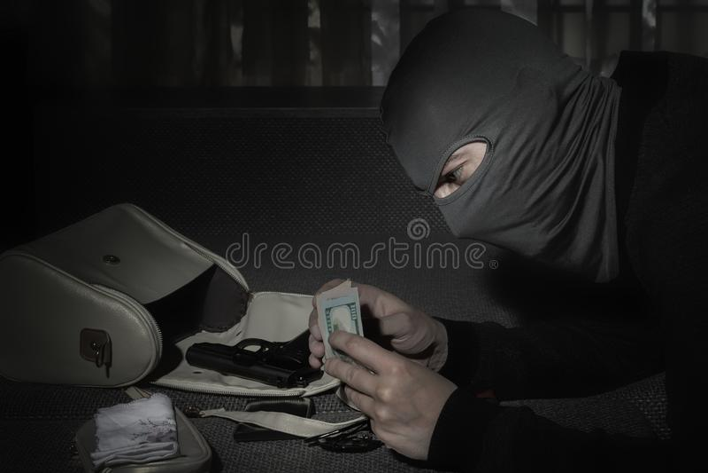 Räuber in einer Maske und mit einer Taschenlampe überprüft den Inhalt der Tasche der Frauen im Raum lizenzfreie stockfotografie