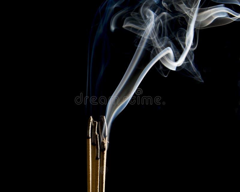 Räucherstäbchen brennen auf dem schwarzen Hintergrund Der Rauch während der Räucherstäbchen, die für brennen, macht Verdienst Bud lizenzfreie stockbilder