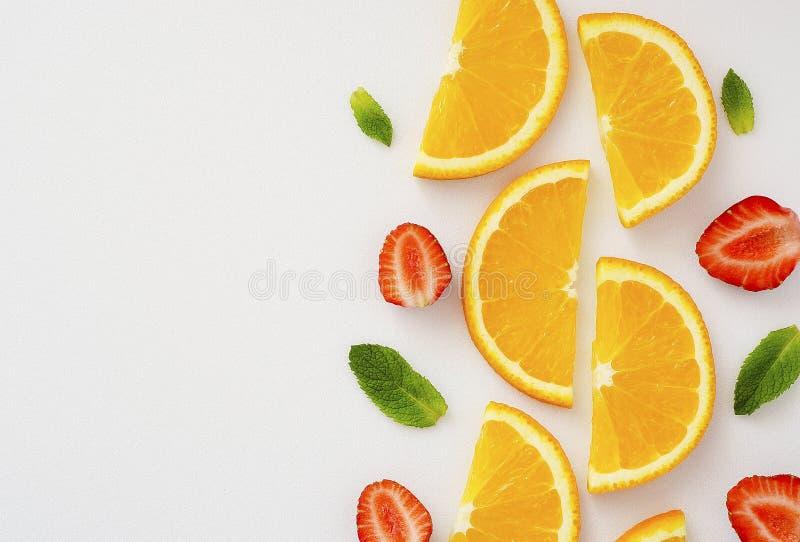Rżnięci pomarańcze, truskawkowych i nowych liście na białym tle 11, fotografia royalty free