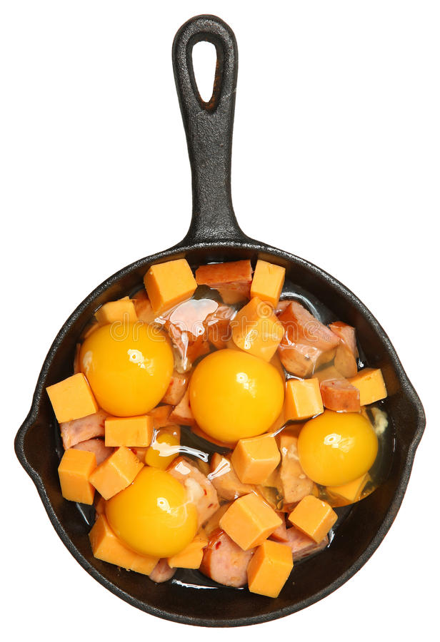 Rå ägg, ost och korv i gjutjärnkastrull arkivbilder