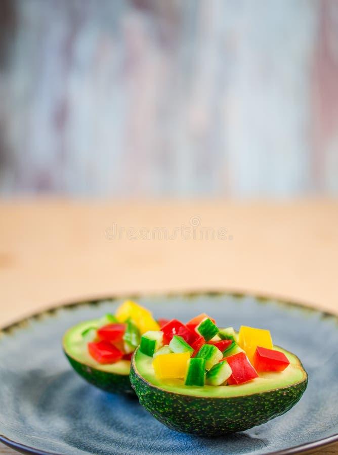 Rå avokado på maträtten arkivbilder