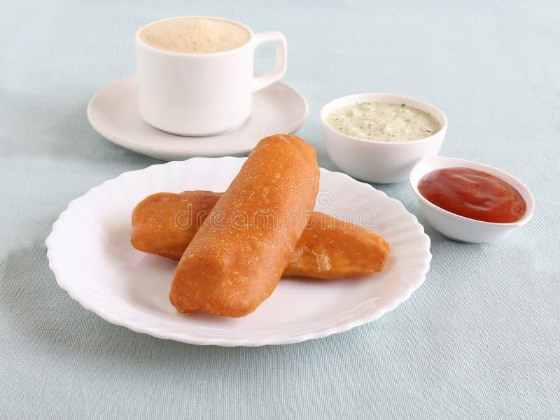 Rå bananstruva för indiskt mellanmål med chutney, ketchup och kaffe fotografering för bildbyråer
