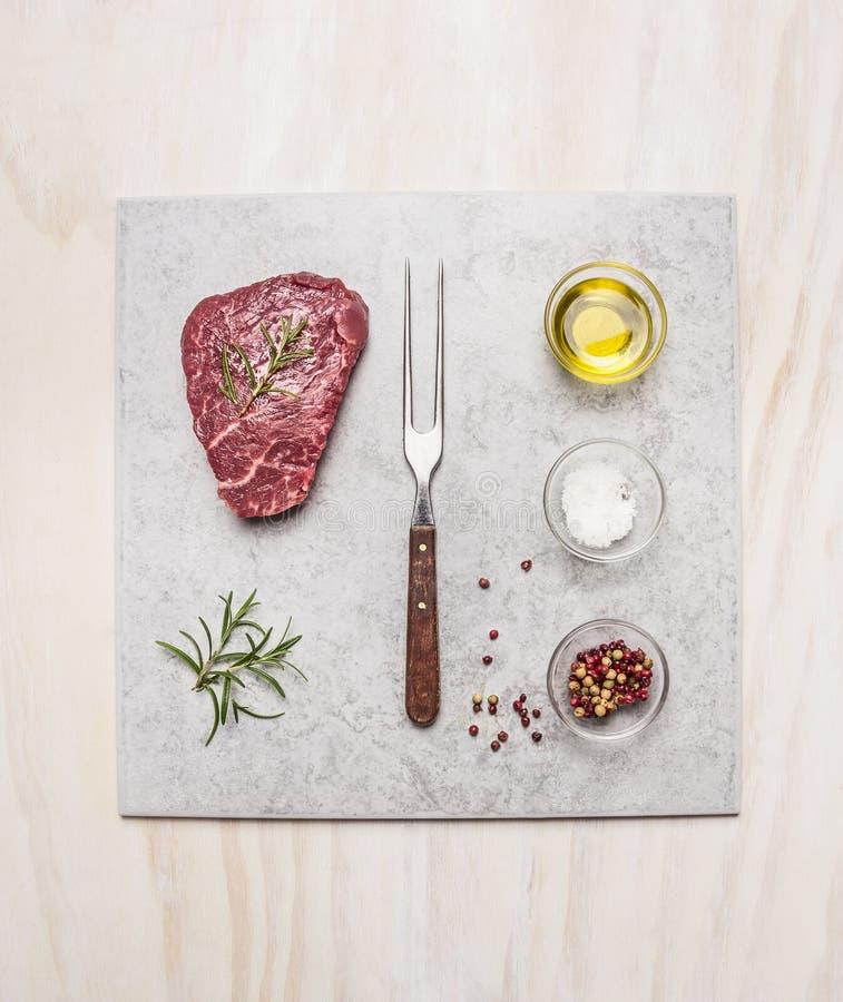 Rå biff för nytt kött med kryddaingredienser på den ljusa marmorplattan över träbakgrund, bästa sikt arkivbilder