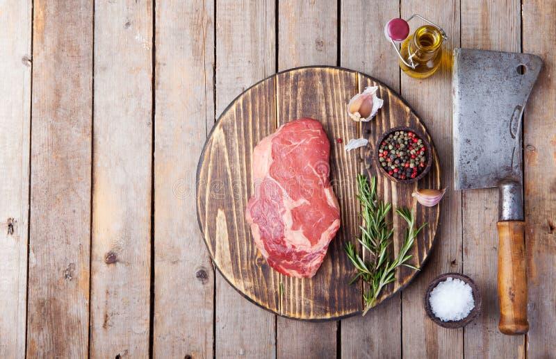 Rå biff för nytt kött med salt och peppar, rosmarin och tomater på skärbrädakopieringsutrymme Top beskådar royaltyfri bild