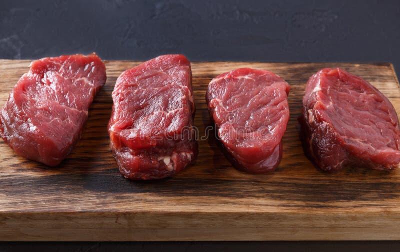 Rå biffar för nötköttfiletmignon på träbräde på grå bakgrund arkivbild