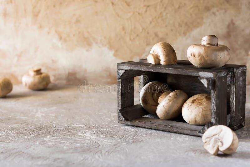 Rå champignons på en lantlig träask arkivfoto
