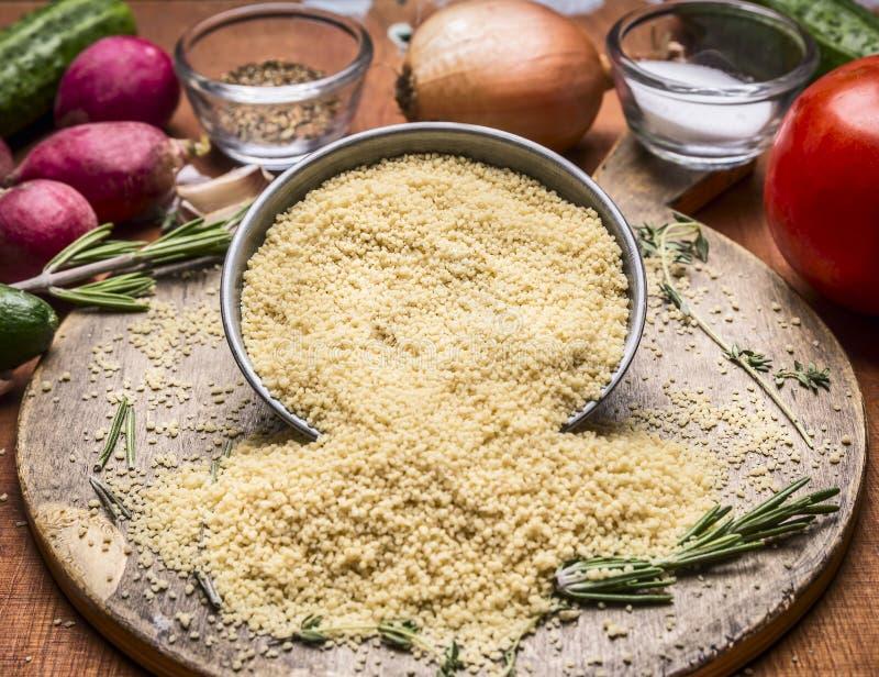 Rå couscoussmulpajer från järn bowlar skärbrädan mot bakgrunden av höstgrönsaker och nära övre för smaktillsats arkivfoton