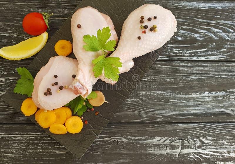 Rå feg fot organisk gödkyckling som är traditionell på en träbrädebakgrund, morötter, citron, persilja, peppar royaltyfri foto