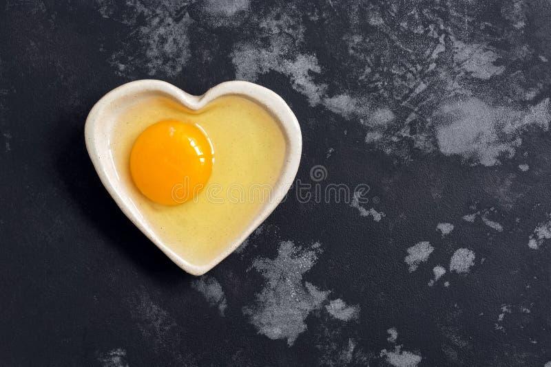 Rå fega ägg i hjärtaformbunke på svärtar konkret bakgrund för grå färger Bästa sikt, kopieringsutrymme royaltyfri fotografi