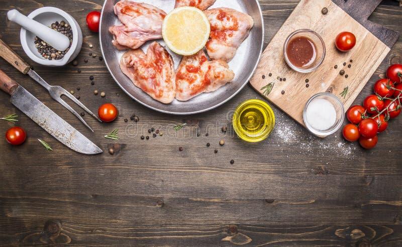 Rå fega vingar med grillfestsås med peppar, örter, en kniv och gaffeln, smör, örter, körsbärsröda tomater på trälantlig backg fotografering för bildbyråer