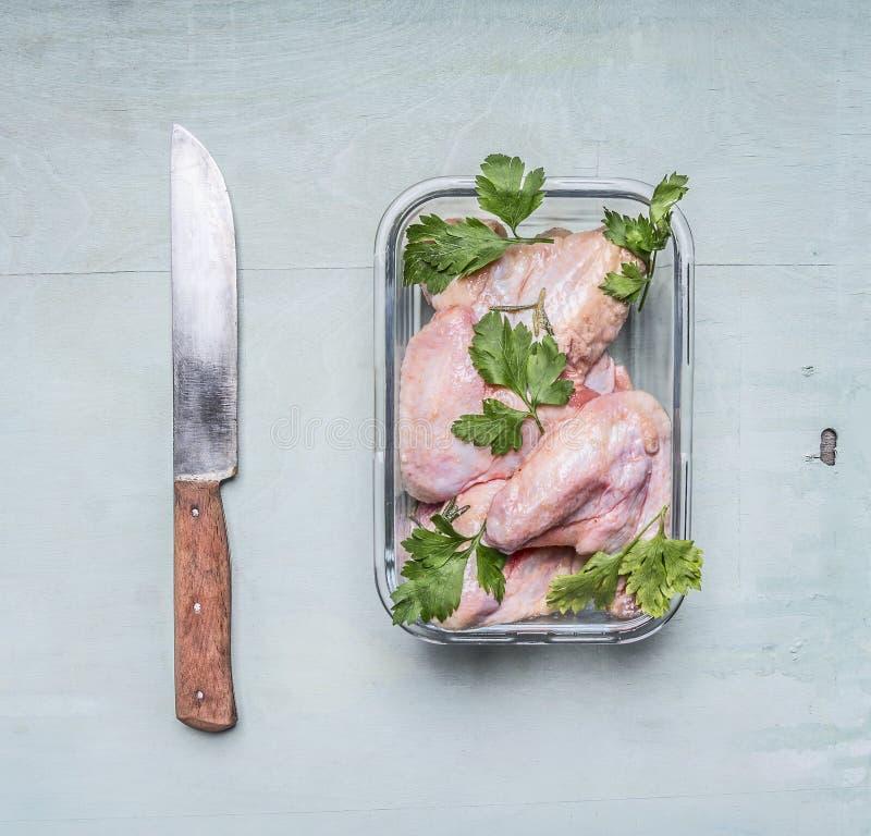 Rå fega vingar med persilja i en genomskinlig bunke med en kökkniv på rusti? träslut för bästa sikt för bakgrund upp royaltyfria bilder