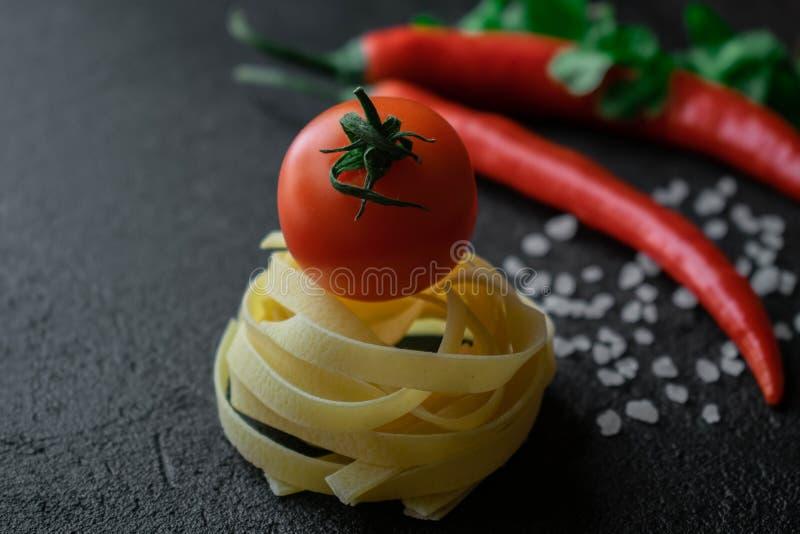 Rå fettuccinepasta med den nya tomaten, det grova havet saltar gröna sidor av koriander och chilipeppar arkivfoto