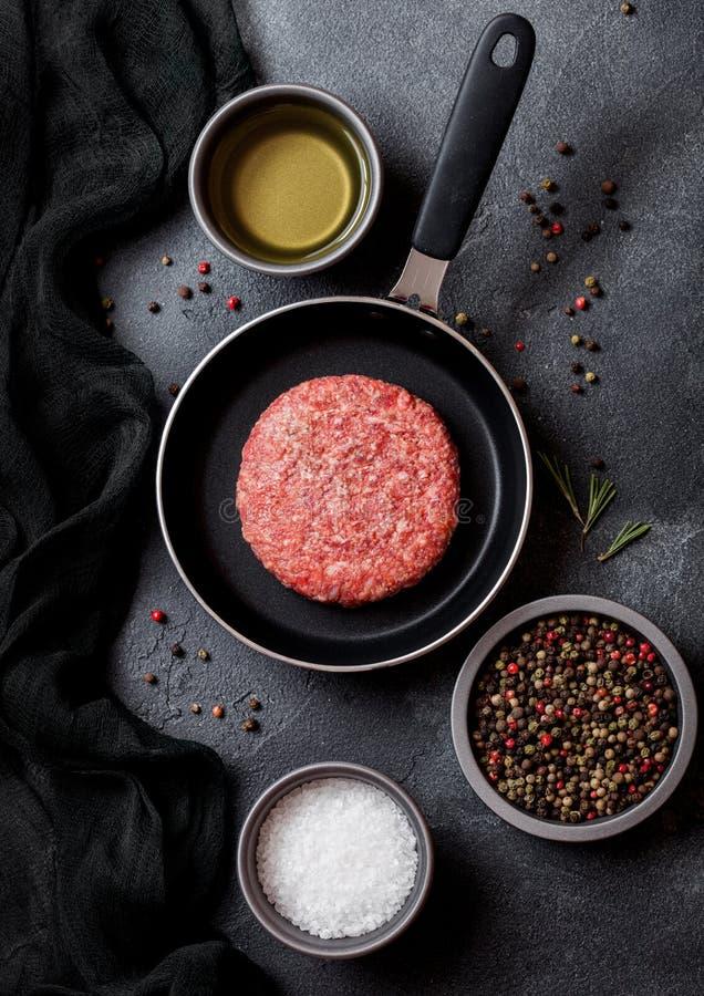 Rå finhackad hemlagad gallernötkötthamburgare i stekpanna Top beskådar Med salt peppar som är salt och arkivfoton