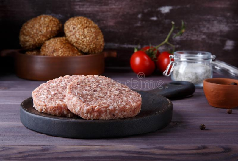 Rå finhackade kotletter för nötköttkötthamburgare på mörk träbakgrund royaltyfri fotografi