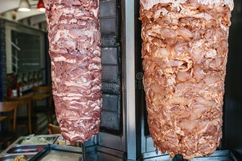 Rå foods för utomhus- shawarma - två sorter av kött på vertikalt galler på kökbakgrund med grönsaker i rostfritt royaltyfria bilder