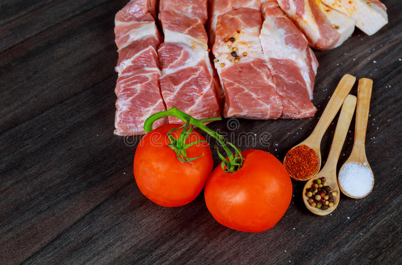 Rå grisköttbaconskivor, skinkskivor, kryddor, pepparkorn, vitlök, sidor för fjärdlager och röda nya körsbärsröda tomater royaltyfria bilder