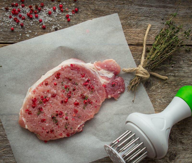Rå grisköttbiff med rosa färger pepprar och det salta havet royaltyfri bild