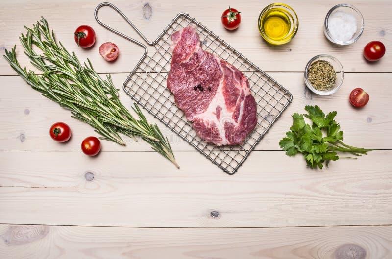 Rå grisköttbiff på gallret för att laga mat med rosmarin, körsbärsröda tomater och kryddor, hel peppargräns, ställetext på trä royaltyfri bild