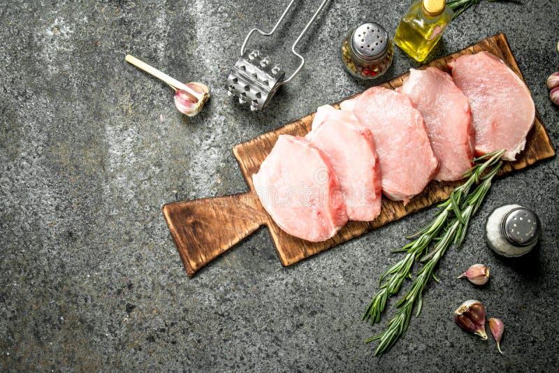 Rå grisköttbiffar med örter och kryddor royaltyfria bilder