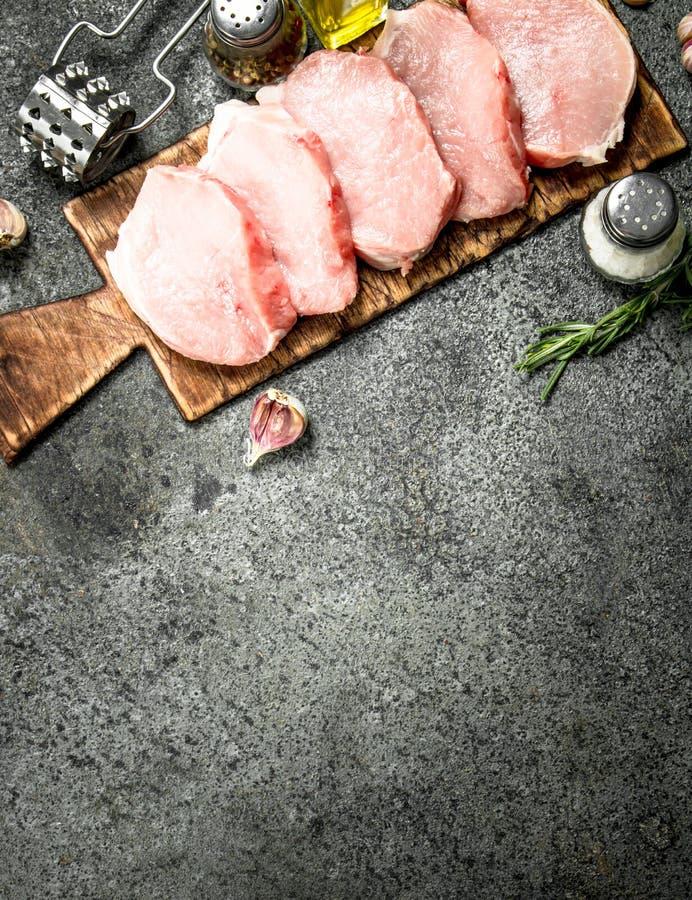 Rå grisköttbiffar med örter och kryddor royaltyfria foton