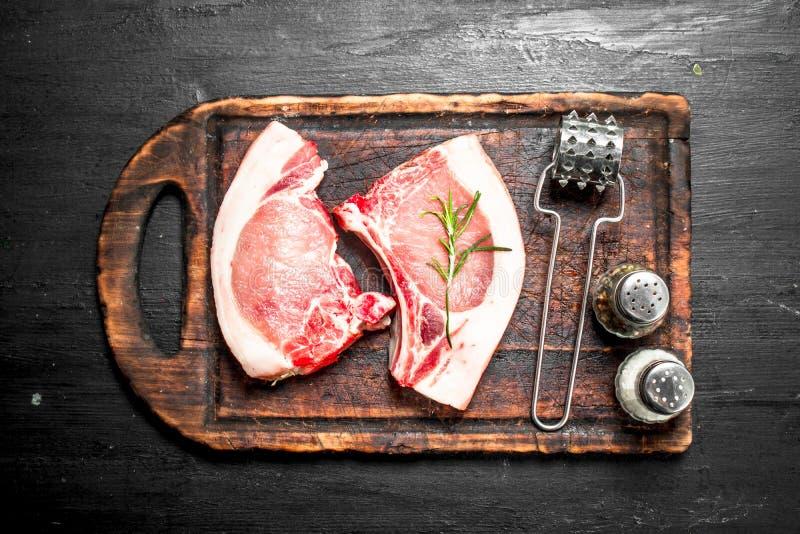 Rå grisköttbiffar på en skärbräda royaltyfria foton