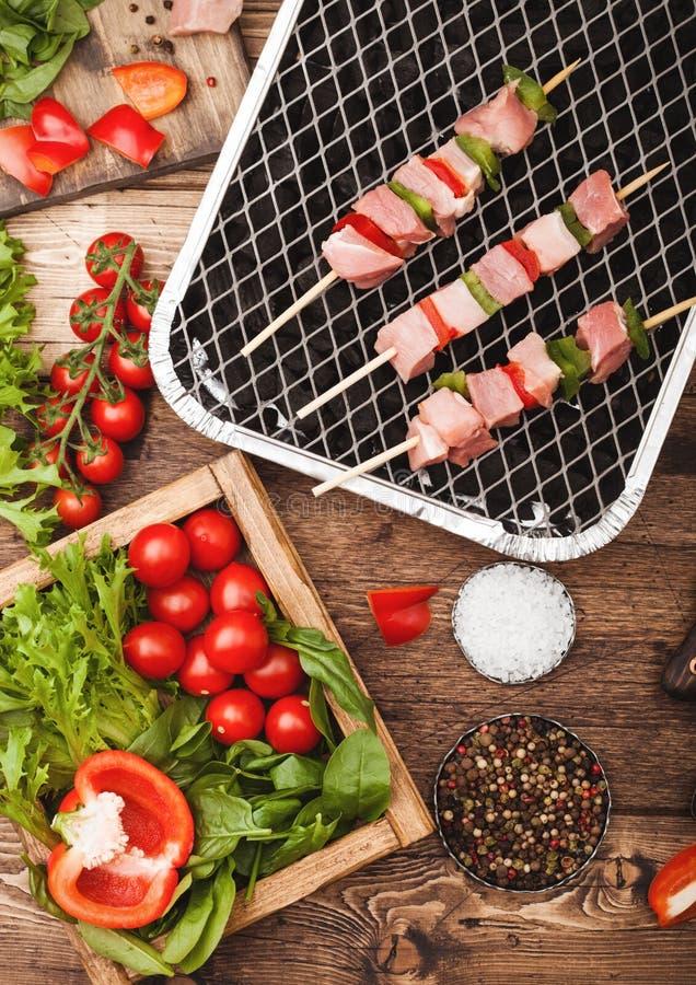 Rå grisköttkebab med paprika på disponibelt kolbbq-galler med nya grönsaker på träbakgrund med gaffeln och kniven Salta och arkivbilder