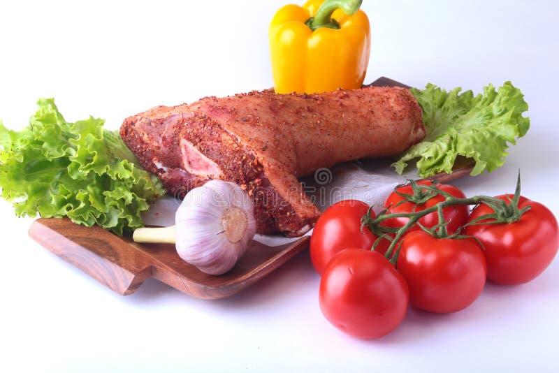 Rå grisköttknoge och grönsaker, vitlök, tomater, spansk peppar kryddor och grönsallatsidor på en skärbräda selektivt arkivfoton