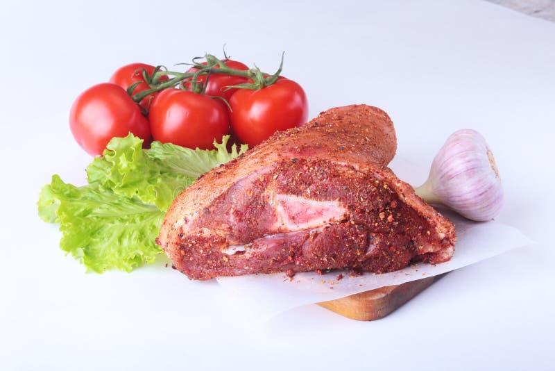 Rå grisköttknoge och grönsaker, vitlök, tomatkryddor och grönsallatsidor på en skärbräda Selektivt fokusera klart royaltyfri bild