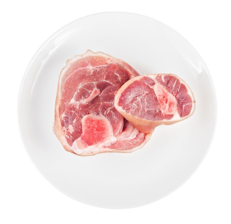 Rå grisköttknoge på plattan som isoleras på vit fotografering för bildbyråer