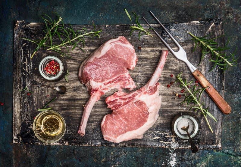 Rå grisköttkotlett med olja och kryddor för galler eller matlagning på lantlig bakgrund, bästa sikt royaltyfri bild