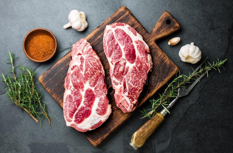 Rå grisköttkotlettkotlett för gallerBBQ med örter på träbräde, kritiserar bakgrund, bästa sikt arkivbild