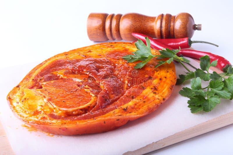 Rå grisköttskinka med kryddor, persiljasidor, chili och kryddamolar som är klar för att grilla för BBQ som isoleras på vit bakgru fotografering för bildbyråer