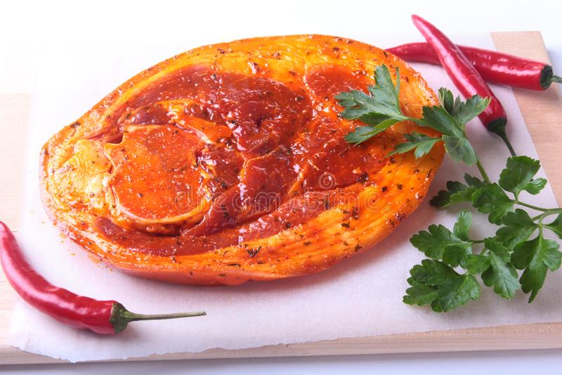 Rå grisköttskinka med kryddor, persiljasidor och chili som är klara för att grilla för BBQ som isoleras på vit bakgrund arkivfoton