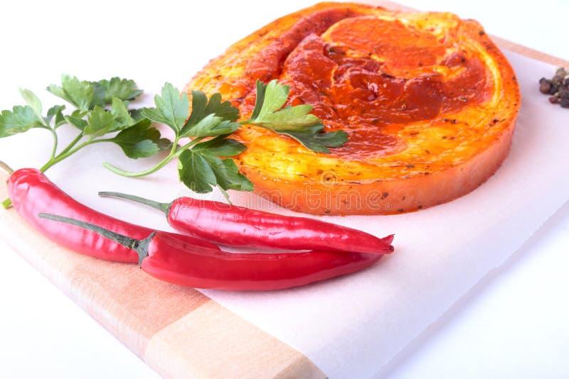Rå grisköttskinka med kryddor, persiljasidor och chili som är klara för att grilla för BBQ som isoleras på vit bakgrund arkivbilder