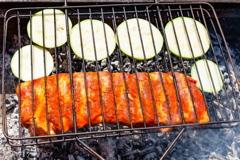Rå grisköttstöd med den skivade zucchinin i galler arkivbild