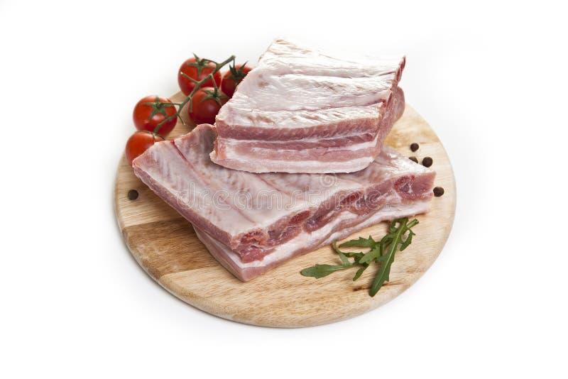 Rå grisköttstöd på en vit bakgrund arkivfoto